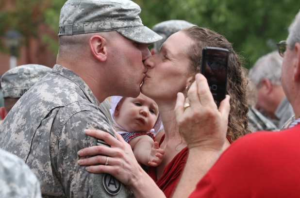 First Lt. Jacob Condon kisses his wife, Heather, while he holds his 5-monthold daughter, Olivia, on Saturday, Aug. 25, 2012 at Columbia College. Condon arrived home with the 175th Military Police Battalion, which is headquartered in Columbia, after a year's deployment in Qatar.